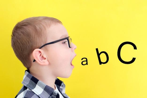Orthophonie. un tout-petit dit bouche ouverte avec des lettres. cours avec un orthophoniste. garçon sur fond jaune isolé