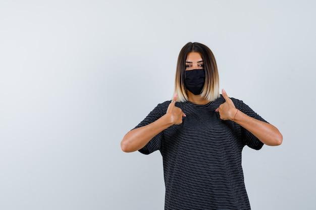 Ortrait de dame pointant sur elle-même en robe noire, masque médical et à la vue de face confiante