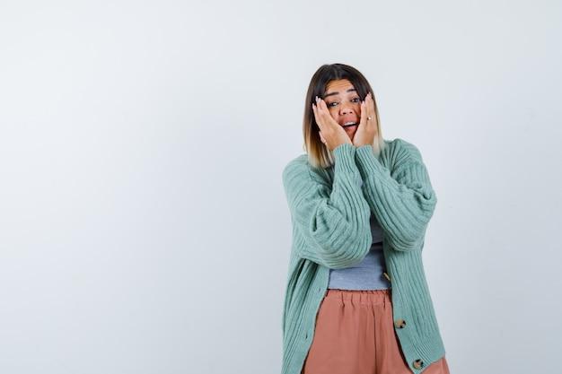 Ortrait de femme gardant les mains sur les joues dans des vêtements décontractés et à la vue de face excitée