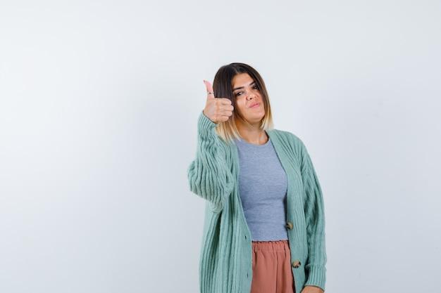 Ortrait de femme montrant le pouce vers le haut dans des vêtements décontractés et à la vue de face heureux