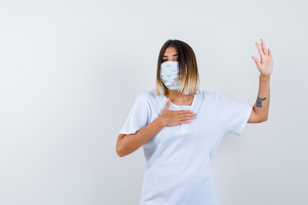 Ortrait de jeune femme montrant le geste d'arrêt en t-shirt, masque et à la vue de face sérieuse
