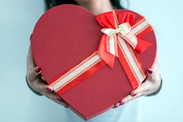 Ortrait de jeune femme souriante heureuse boîte cadeau rouge tenir.