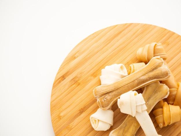 Os de nourriture pour chien sur couper du bois sur blanc