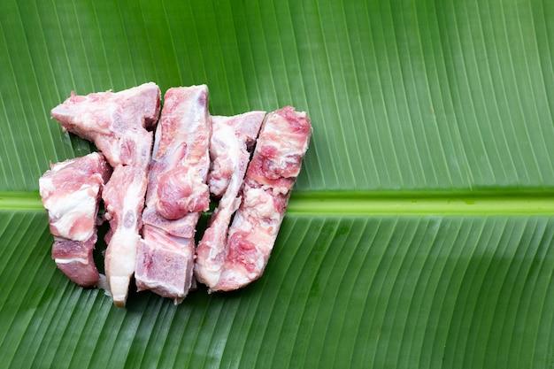 Os de porc cru sur feuille de bananier
