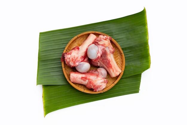 Os de porc crus dans un panier en bambou sur des feuilles de bananier