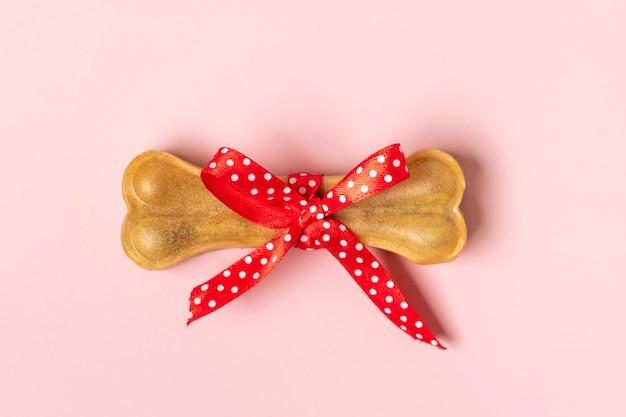 Os pour chiens avec arc rouge isolé