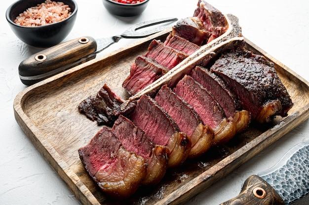 Os de t moyen grillé ou ensemble de steak porterhouse, sur une table en pierre blanche