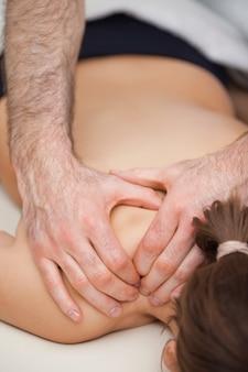Ostéopathe appuyant sur les épaules de son patient tout en utilisant ses deux mains