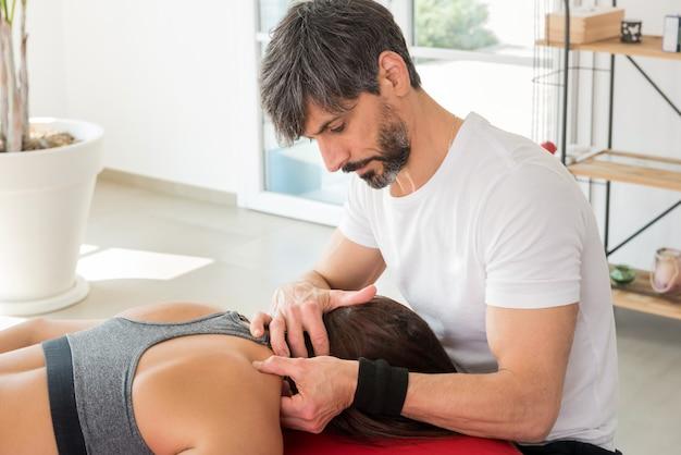 Ostéopathe effectuant un traitement des points de déclenchement sur un patient en appliquant une pression avec ses doigts sur les muscles pour soulager la tension et la douleur dans un concept de carrière pour la médecine alternative