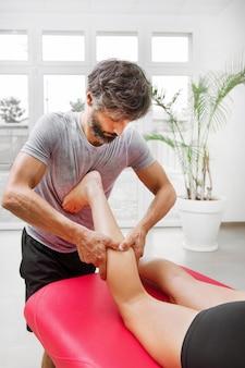 Ostéopathe masculin effectuant un massage myofascial du mollet sur une jeune femme manipulant les muscles avec ses mains lors d'une consultation
