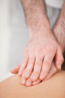 Ostéopathe masser son patient en appuyant sur son dos