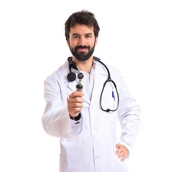 Oto-rhino-laryngologiste avec son otoscope sur fond blanc