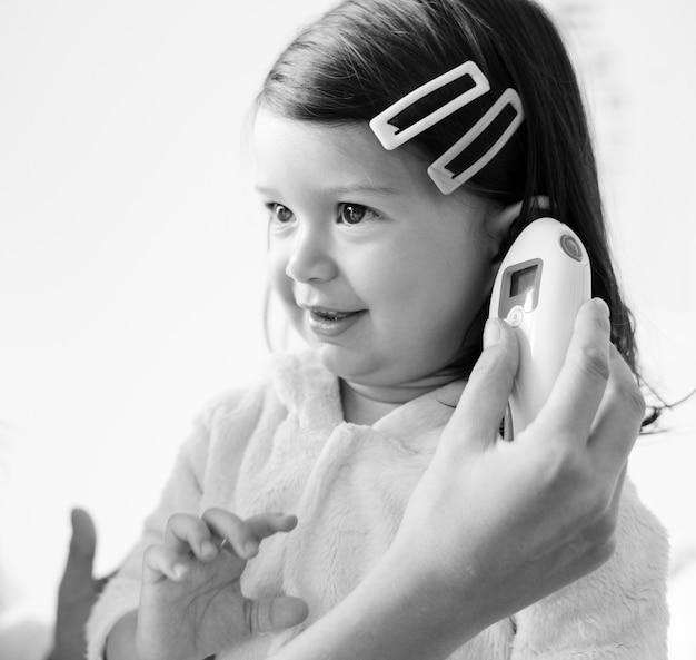Oto-rhino-laryngologiste vérifiant une douce petite fille