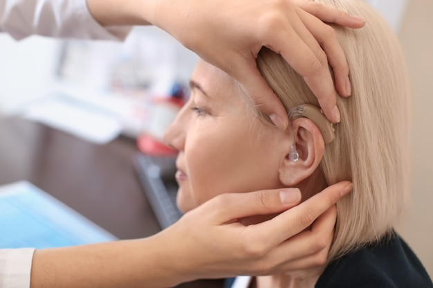Otolaryngologist mettant l'aide auditive dans l'oreille de la femme à l'hôpital