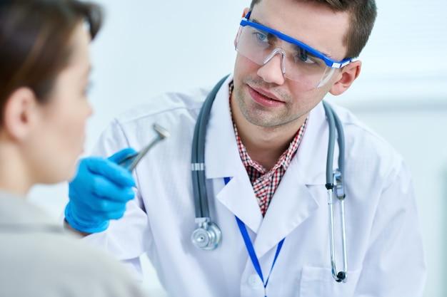 Otolaryngologue examinant le patient