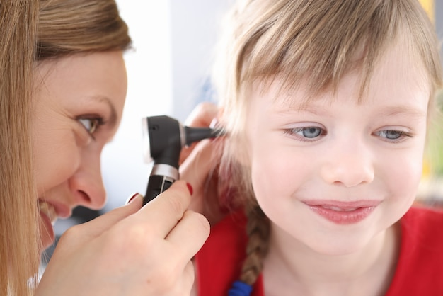 Otorhinolaryngologist regardant l'oreille douloureuse de la petite fille