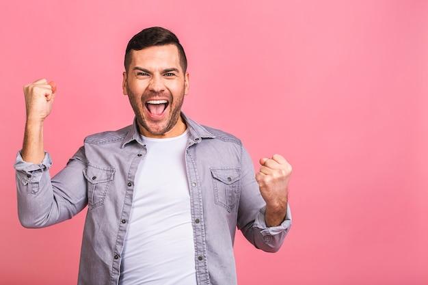 Ouais heureux gagnant heureux jeune bel homme célébrant la victoire en faisant des gestes et en gardant la bouche ouverte