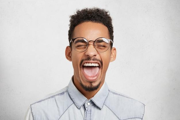 Ouais! portrait de ravissant mâle à la peau sombre heureux ferme les yeux et ouvre largement la bouche, montre les dents et la langue