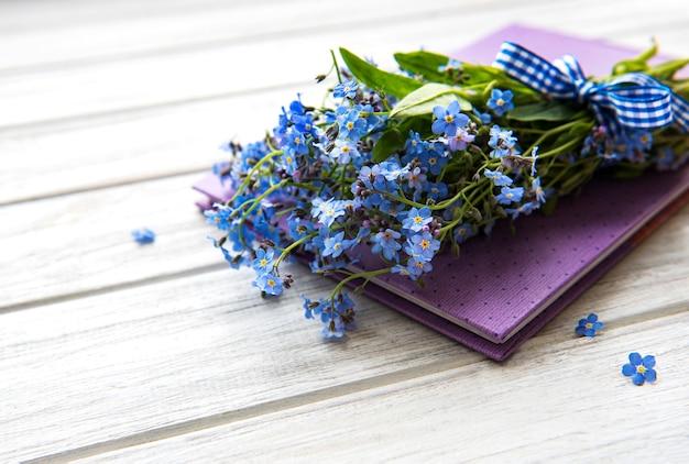 Oubliez-moi pas de fleurs et de cahier sur bois blanc