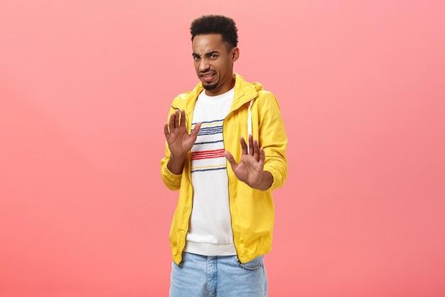 Ouf, enlève-le-moi. picky dégoûté intense beau mâle élégant avec une barbe dans une veste jaune urbaine à la mode tirant les mains dans un geste de non ou de refus fronçant le nez dans l'aversion sur le mur rose
