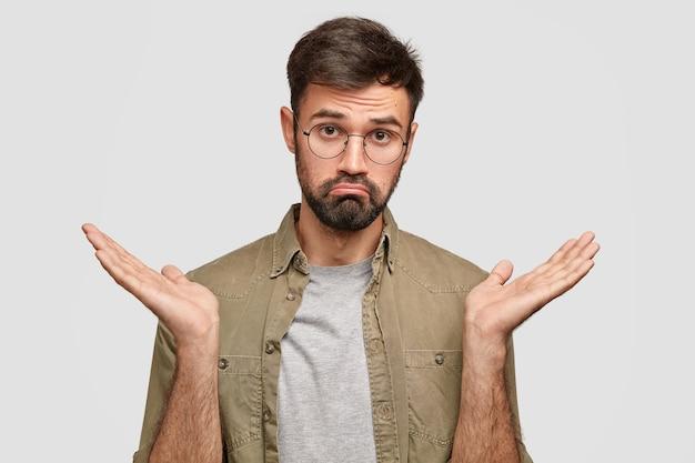 Oui ou non? un jeune homme hésitant perplexe hausse les épaules et serre les lèvres, semble douteux et incertain, tente de prendre une décision