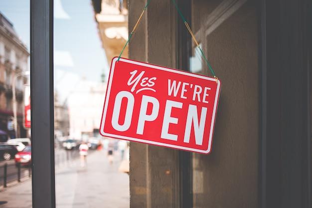 Oui, nous sommes ouverts signe sur la vitre des portes en magasin.