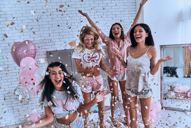 Oui! quatre jeunes femmes séduisantes en pyjama souriant et faisant des gestes en sautant dans la chambre avec des confettis volant partout