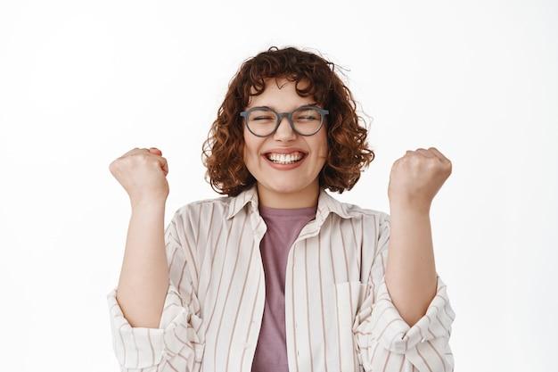 Oui succès. une fille moderne souriante et excitée célèbre la victoire, fait pomper le poing pour triompher de l'objectif, profite de la victoire, devient gagnante, debout sur blanc