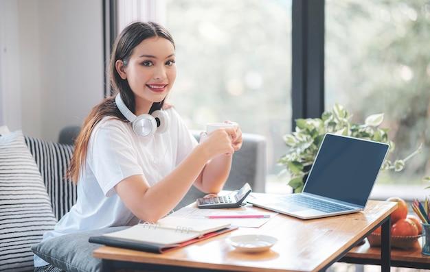 Oung belle femme asiatique tenant une tasse, souriant et regardant la caméra tout en étant assis et travaillant avec un ordinateur portable dans le salon à la maison.
