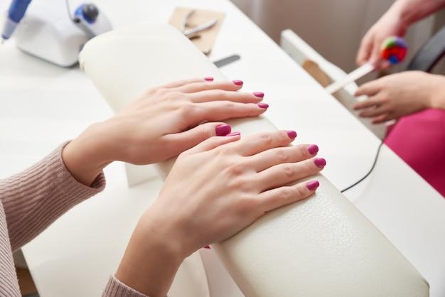 Oung femme faisant manucure dans le salon. concept de beauté.