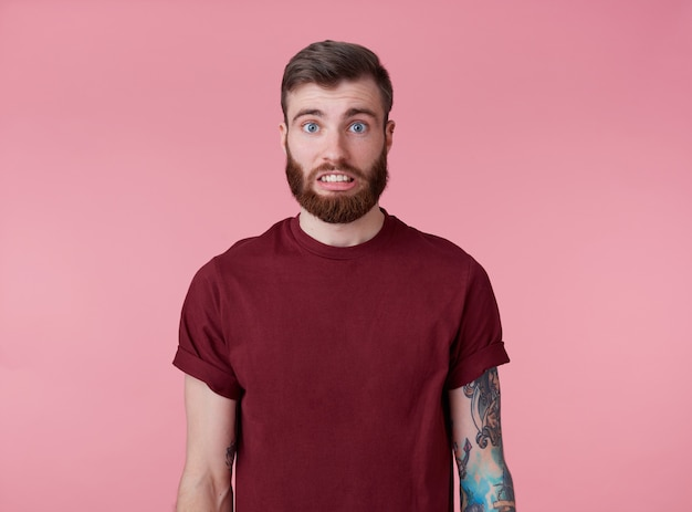 Oups! quelque chose ne va pas! portrait de jeune homme barbu tatoué attrayant en t-shirt blanc, a l'air désolé et triste, se dresse sur fond rose.