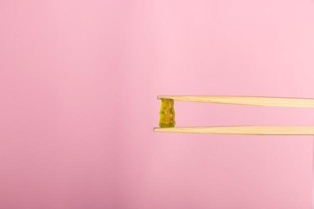 Ours gommeux pris avec des bâtons sur fond rose rose