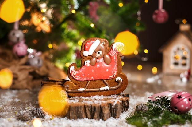 Ours de noël en pain d'épice en traîneau dans une décoration chaleureuse avec des guirlandes