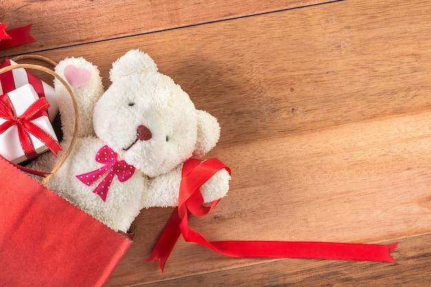 Ours en peluche et boîtes-cadeaux dans le sac à provisions sur table en bois