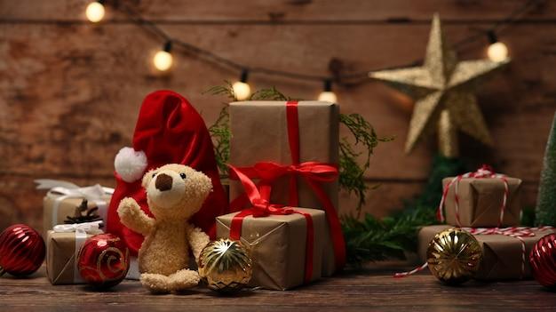Ours en peluche, bonnet de noel rouge et coffrets cadeaux de noël sur table en bois.