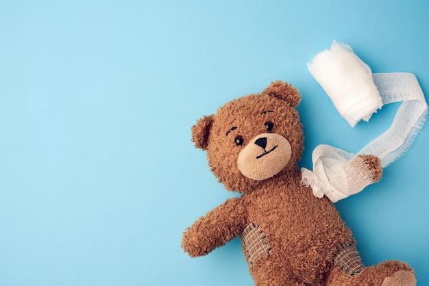 Ours en peluche bouclé brun vintage drôle avec patte rembobinée avec un bandage de gaze blanche sur fond bleu