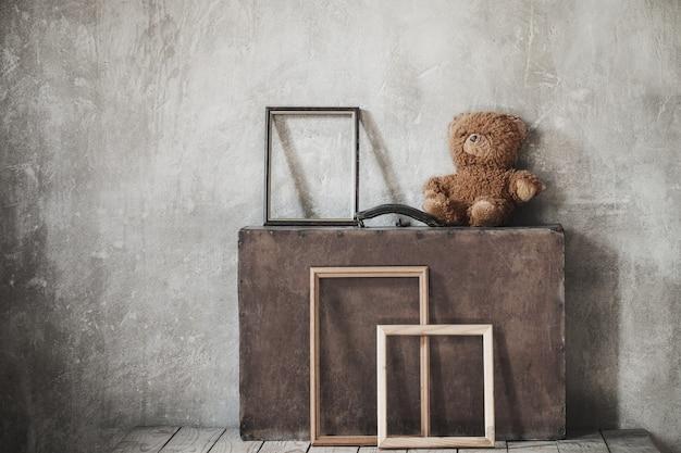 Ours en peluche brouwn, vieille valise et cadres en bois