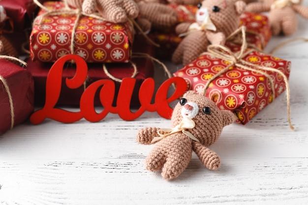 Ours en peluche brun avec boîte-cadeau rouge sur blanc