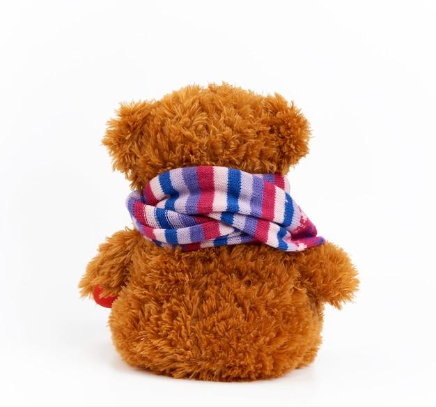 Ours en peluche brun bouclé est assis avec son dos