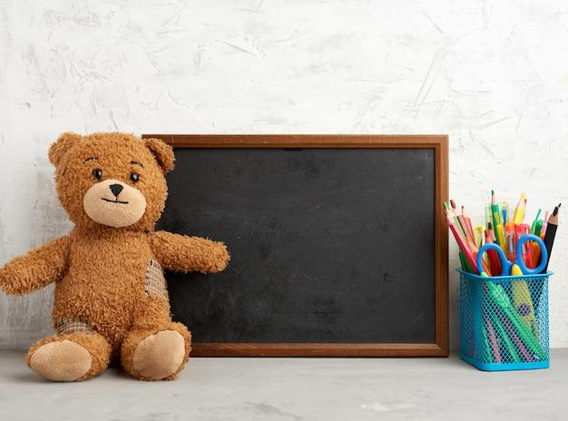 Ours en peluche brun et cadre rectangulaire en bois vide, tableau noir pour écrire une liste de choses à faire