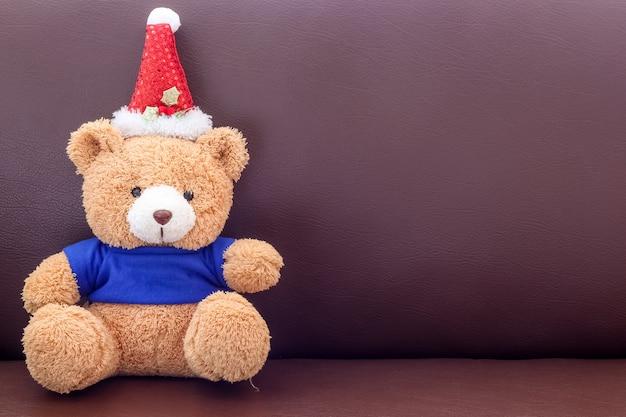 Ours en peluche brun avec une chemise bleue portant un chapeau de noël sur le canapé