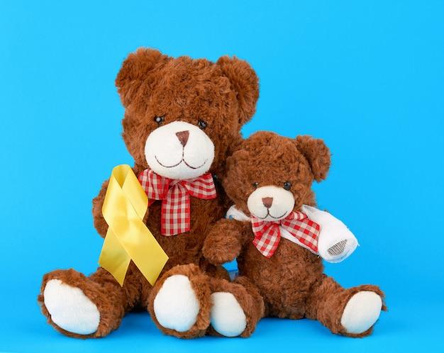 Ours en peluche brun est assis et tient dans sa patte un ruban de soie jaune sur un fond bleu