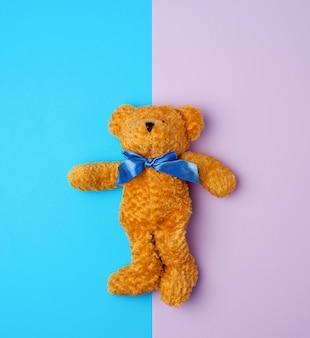 Ours en peluche brun mignon avec un arc bleu sur son cou