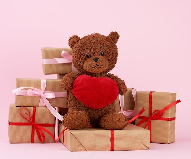 Ours en peluche brun mignon et cadeau dans une boîte enveloppée dans du papier écologique marron, attaché avec un ruban rouge en soie