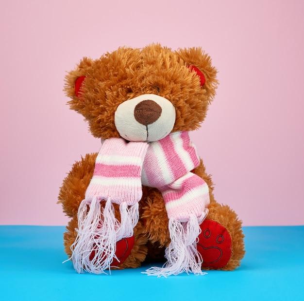 Ours en peluche brun mignon dans une écharpe en tricot de couleur assis