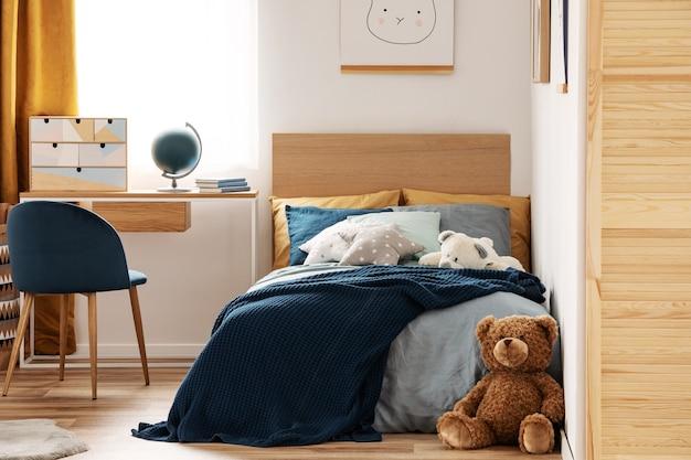 Ours en peluche brun mignon sur parquet de l'intérieur de la chambre élégante pour les enfants