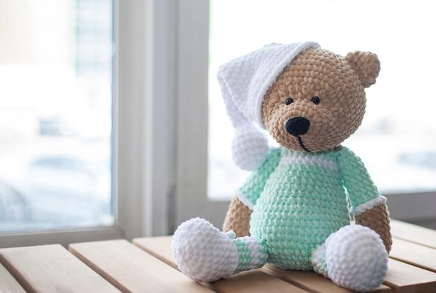 Ours en peluche brun en peluche dans des vêtements lilas et un chapeau blanc sur le bois.