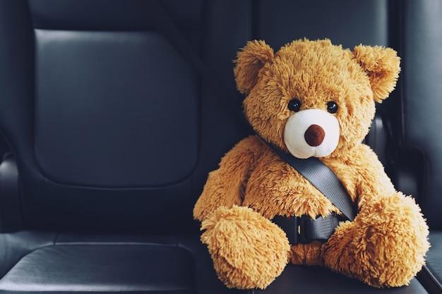 Ours en peluche brun portant la ceinture de sécurité de la voiture