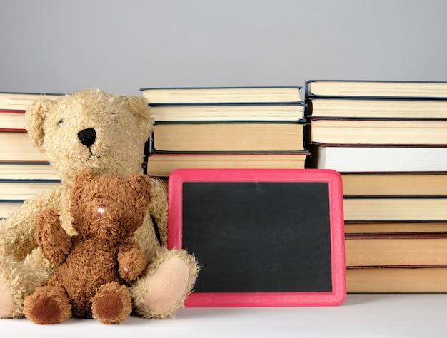 Ours en peluche brun et tableau noir vide dans un cadre rouge sur une pile de livres