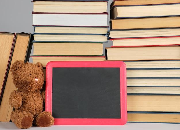 Ours en peluche brun et tableau noir vide dans un cadre rouge sur la pile de livres